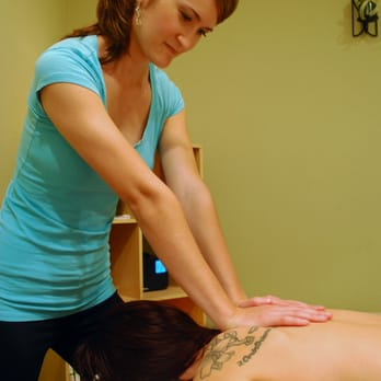 Masseuse pushing on shoulder area of client laying face-down